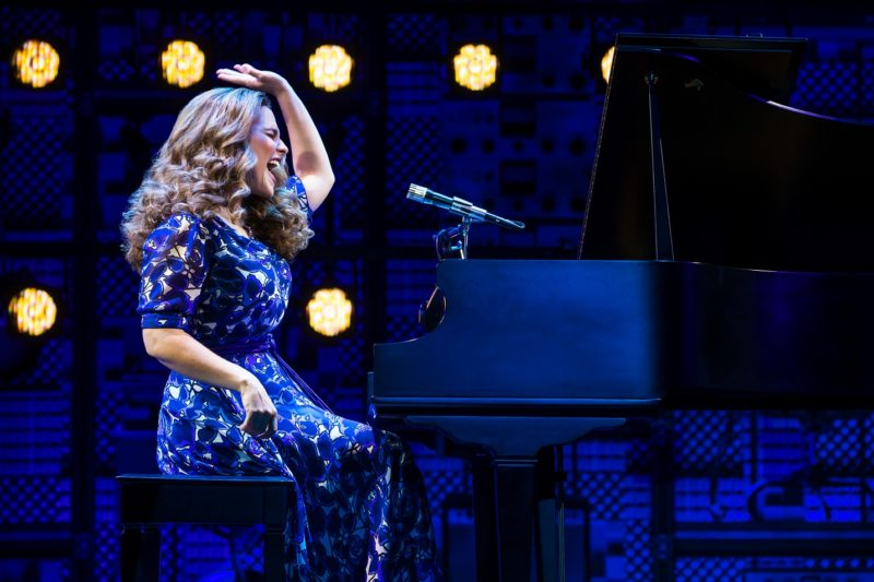 Carole King in present day performs at the piano.