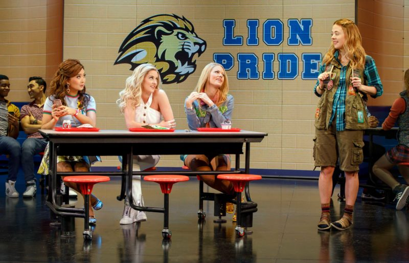 Cady (Erika Henningsen) meets The Plastics - Gretchen (Ashley Park), Regina (Taylor Louderman), and Karen (Kate Rockwell) - who are all seated at a table in the high school cafeteria in a scene from Mean Girls.