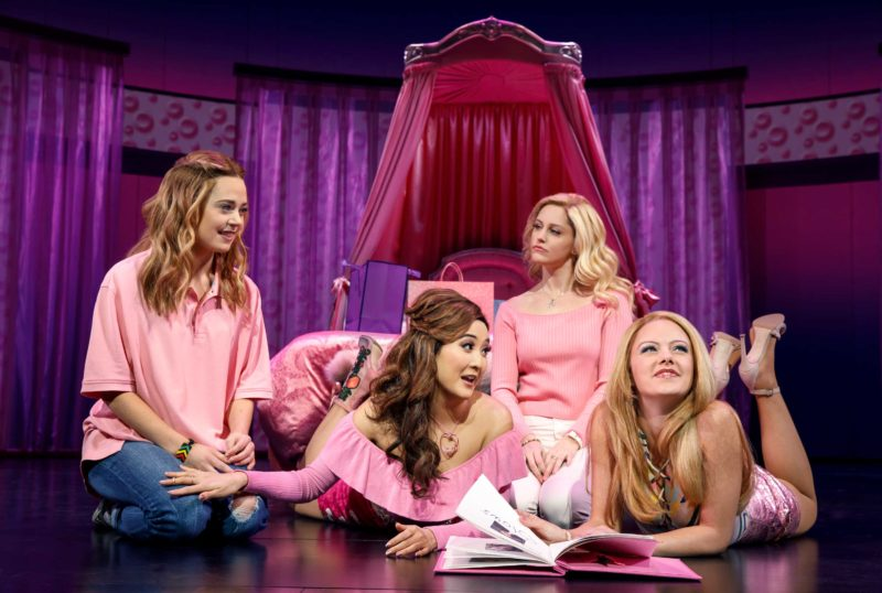 Cady (Erika Henningsen), Gretchen (Ashley Park), Regina (Taylor Louderman), and Karen (Kate Rockwell) gossip about other students and write in the Burn Book in Regina's bedroom in a scene from Mean Girls.