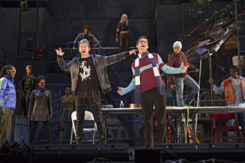 Rodger, wearing a leather jacket, and Mark, wearing eye glasses and a scarf lead the cast in a dance.