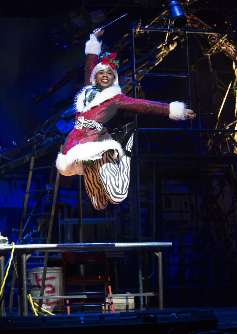 A young drag queen (Angel) dressed in her sexy Santa outfit jumps off the table.