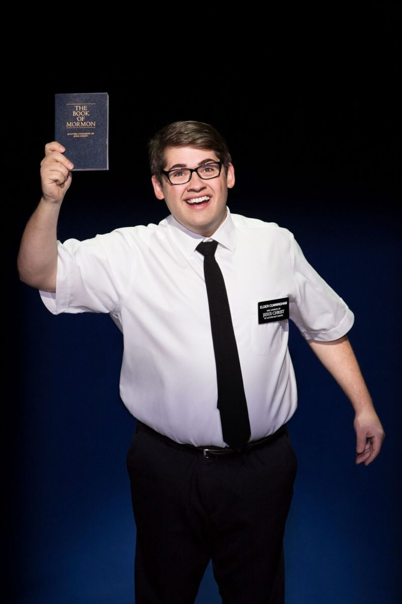 A mormon wearing glasses proudly holds up his copy of The Book of Mormon